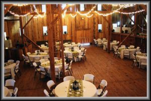 inside of barn set up with tables and chairs