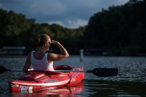 kayaker on the water shielding her eyes from the sun